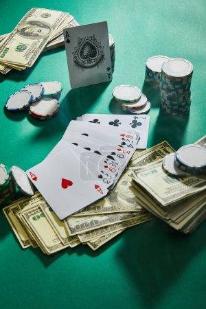 Photo pour Vue grand angle des cartes à jouer, des billets en dollars et des jetons de casino sur vert - image libre de droit
