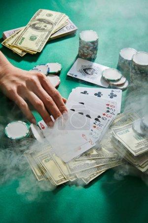 Photo pour Vue recadrée de la main féminine avec des cartes à jouer, de l'argent et des jetons de casino avec de la fumée autour sur vert - image libre de droit
