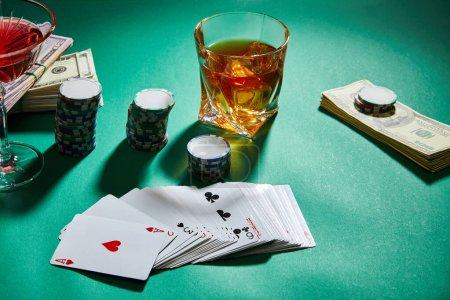 Photo pour Vue à grand angle des verres de cognac et cocktail avec de l'argent, des jetons de casino et des cartes à jouer sur le vert - image libre de droit