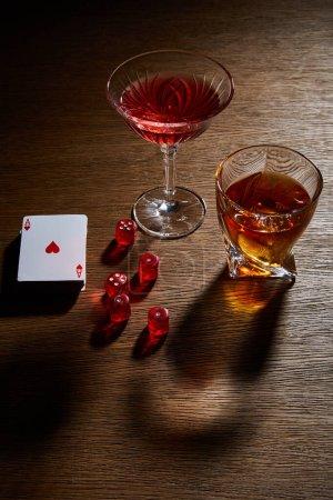 Photo pour Vue grand angle des verres de cognac et cocktail près du jeu de cartes et dés sur fond en bois - image libre de droit