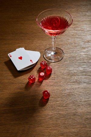 Photo pour Vue grand angle du verre de cocktail près du jeu de cartes et dés sur fond en bois - image libre de droit