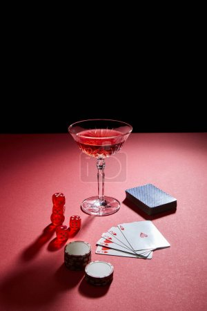Photo for Glass of cocktail near playing cards, casino chips and dice on red surface isolated on black - Royalty Free Image