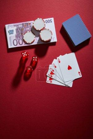 Photo pour Vue du dessus des cartes à jouer, dés, jetons de casino et billets de banque sur rouge - image libre de droit