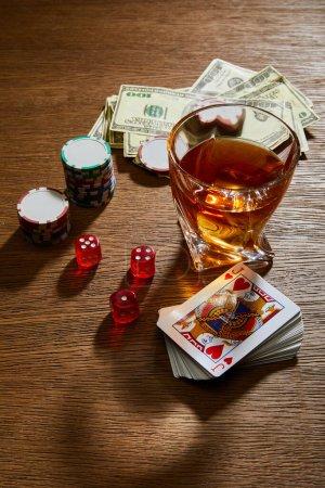 Photo pour Vue en angle élevé du verre de cognac près des billets en dollars, des cartes à jouer, des jetons de casino et des dés sur fond en bois - image libre de droit