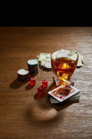 Photo pour Vue en angle élevé du verre de cognac près des billets en dollars, du jeu de cartes, des jetons de casino et des dés sur une surface isolée sur du noir - image libre de droit
