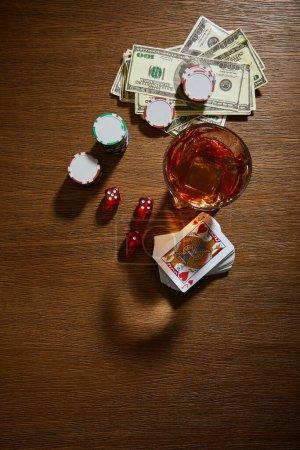 Photo pour Vue du dessus du verre de cognac près des billets en dollars, du jeu de cartes, des jetons de casino et des dés sur fond en bois - image libre de droit