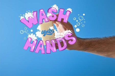 Photo pour Vue recadrée de l'homme tenant du savon isolé sur bleu, illustration mains lavées - image libre de droit