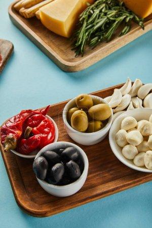Blick auf Schüsseln mit Oliven, Mozzarella und marinierten Chilischoten mit Antipasto-Zutaten auf Platten auf blauem Grund