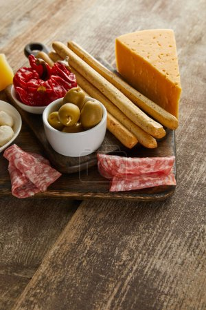 Photo for High angle view of breadsticks with antipasto ingredients on boards on wooden background - Royalty Free Image