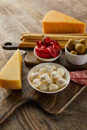 Foto de Vista de gran angular de los cuencos con ingredientes antipasto cerca del queso, las lonchas de salami y los palillos en las tablas sobre fondo de madera. - Imagen libre de derechos