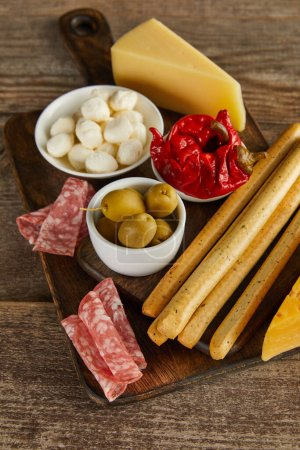 High angle view of bowls with antipasto ingredients with breadsticks, salami slices and cheese on boards on wooden background