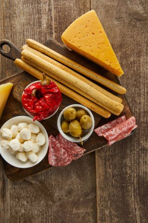 Photo for Top view of bowls with antipasto ingredients near breadsticks, salami slices and cheese on boards on wooden background - Royalty Free Image
