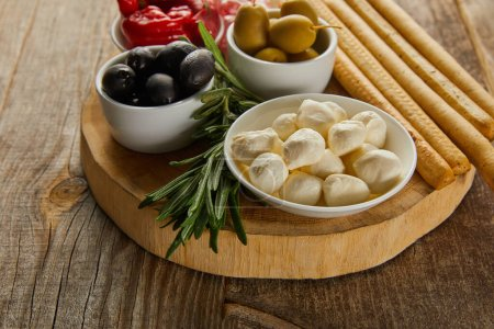 Photo for Round board with rosemary, breadsticks and bowls with antipasto ingredients on wooden background - Royalty Free Image