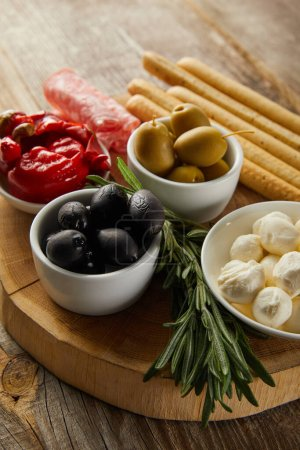 Photo for Selective focus of breadsticks, salami slices and rosemary near bowls with antipasto ingredients on board on wooden background - Royalty Free Image