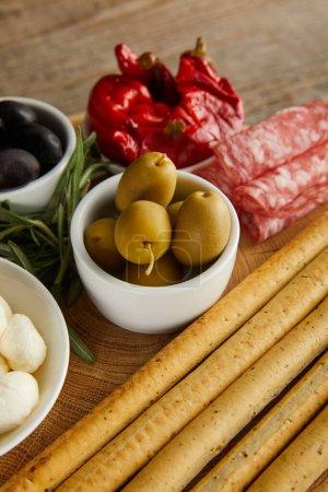 Photo pour Vue grand angle des bâtonnets de pain avec des ingrédients antipasto sur panneau rond sur fond en bois - image libre de droit
