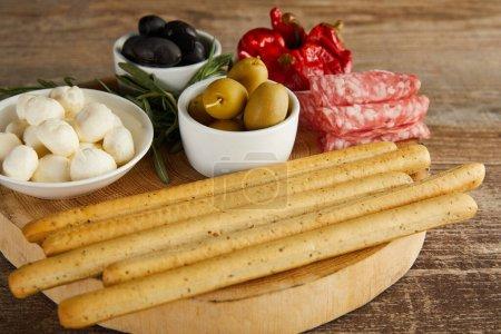 Photo pour Planche ronde avec bâtonnets de pain, tranches de salami, verdure et bols avec des ingrédients antipasto sur fond en bois - image libre de droit