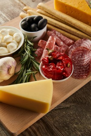 Photo for High angle view of board with breadsticks, cheese and antipasto ingredients on wooden background - Royalty Free Image