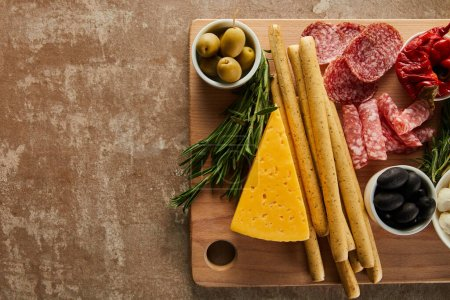 Photo for Top view of board with breadsticks, cheese and antipasto ingredients on brown background - Royalty Free Image