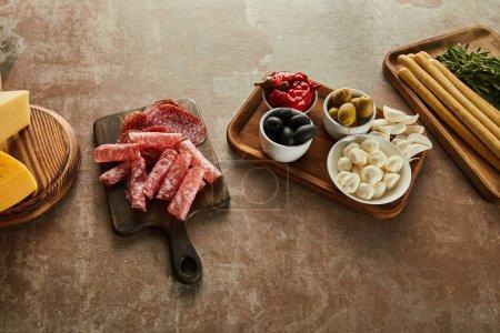 Foto de Vista de gran angular de los ingredientes antipasto en los tableros de marrón - Imagen libre de derechos