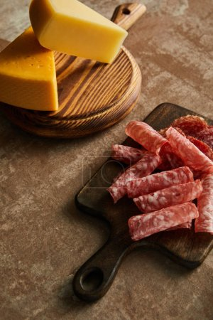 High angle view of boards with salami slices and cheese on brown