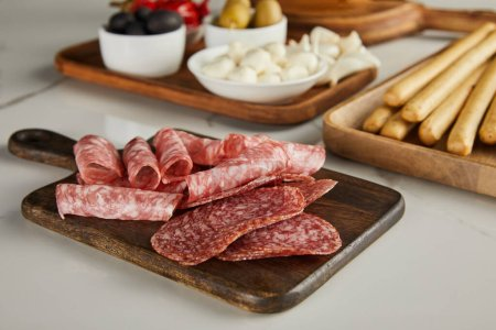 Photo for Selective focus of salami slices on board near antipasto ingredients on white - Royalty Free Image