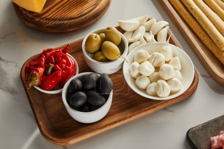 Photo for High angle view of boards with breadsticks, garlic and bowls with olives, mozzarella and marinated chili peppers on white - Royalty Free Image