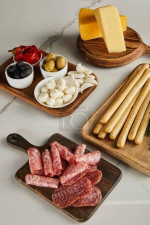 Photo pour Vue en angle élevé des planches avec des bâtonnets de pain, des tranches de salami, du fromage et des ingrédients antipasto sur blanc - image libre de droit