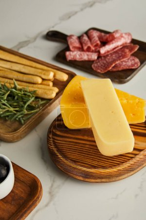Photo for High angle view of boards with cheese and antipasto ingredients on white background - Royalty Free Image