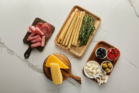 Photo for Flat lay with antipasto ingredients on boards on white - Royalty Free Image