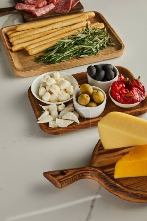 Photo for High angle view of cheese, breadsticks, rosemary, garlic and bowls with antipasto ingredients on boards on white - Royalty Free Image