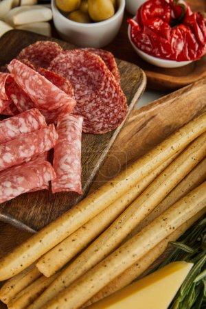Photo pour Vue en angle élevé des tranches de salami, des bâtonnets de pain et des ingrédients antipasto sur les planches - image libre de droit