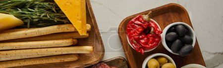 Photo for Top view of breadsticks, cheese, greenery and bowls with antipasto ingredients on boards on white, panoramic shot - Royalty Free Image