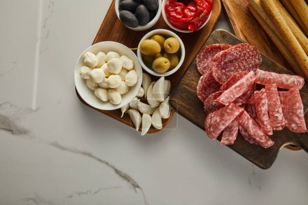 Photo for Top view of salami slices with antipasto ingredients on boards on white - Royalty Free Image