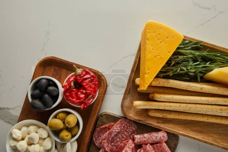 Photo for Top view of salami slices, breadsticks, cheese, greenery and bowls with antipasto ingredients on boards on white background - Royalty Free Image