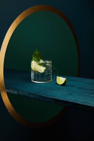 Photo for Glass with refreshing drink with ice cubes, mint leaf and lime slice on wooden surface on geometric blue and green background - Royalty Free Image