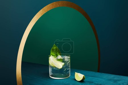 Photo for High angle view of glass with refreshing drink with lime, ice cubes and mint leaf on wooden surface on geometric blue and green background - Royalty Free Image