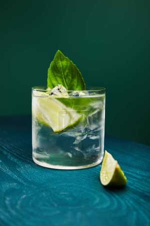 Photo for Close up view of old fashioned glass with drink and lime on blue wooden surface isolated on green - Royalty Free Image