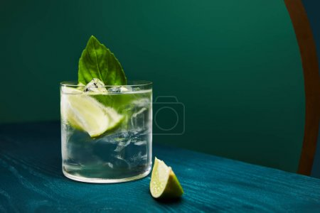close up view of old fashioned glass with drink and lime on blue wooden surface isolated on green