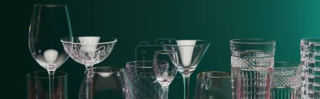 panoramic view of old fashioned glass, cocktail glass, champagne flute, shot glass, highball glass, collins glass, brandy glass, cognac balloon and collins glass isolated on green