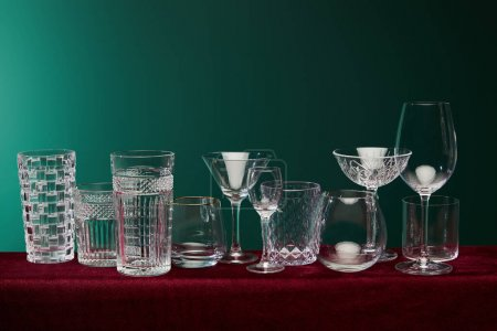 Photo for Set of glasses: old fashioned glass, cocktail glass, champagne flute, shot glass, highball glass, collins glass, brandy glass, cognac balloon and collins glass on green background - Royalty Free Image
