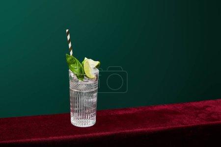 Photo pour Vue en angle élevé du mojito avec glace, menthe, chaux et paille à boire rayée dans un verre de collins isolé sur vert - image libre de droit