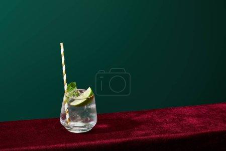 Photo pour Vue à angle élevé de verre à l'ancienne avec bord doré avec mojito et paille à boire rayée isolée sur vert - image libre de droit