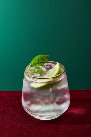 Close up view of old fashioned glass with golden rim with mojito isolated on green
