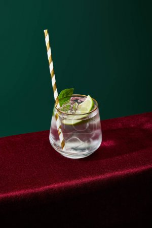 Photo for High angle view of old fashioned glass with golden rim with mojito and striped drinking straw isolated on green - Royalty Free Image