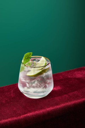 high angle view of mojito with mint and ice in glass isolated on green