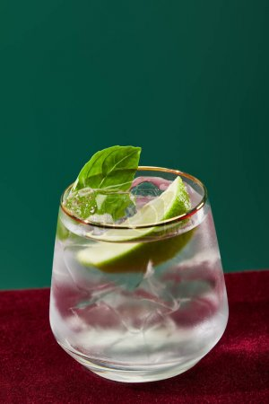 close up view of cold mojito with mint in glass with golden rim isolated on green