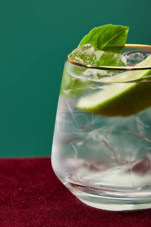 Close up view of refreshing mojito with mint in glass with golden rim isolated on green