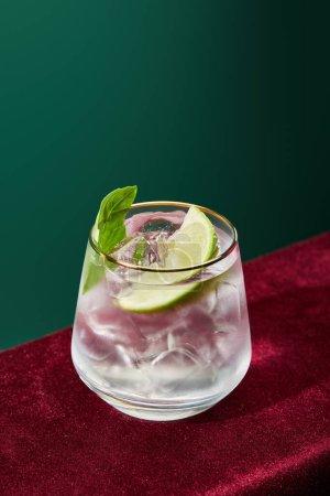 Photo pour Vue à grand angle de mojito rafraîchissant avec menthe et glace en verre avec bord doré isolé sur vert - image libre de droit