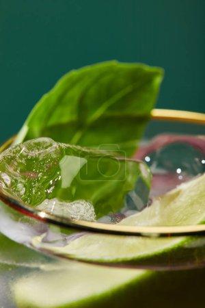 Photo pour Vue rapprochée du verre recadré avec mojito rafraîchissant, menthe et tranche de citron vert isolé sur vert - image libre de droit
