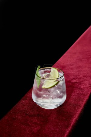 High angle view of  old fashioned glass with refreshing mojito, mint and lime slice isolated on black
